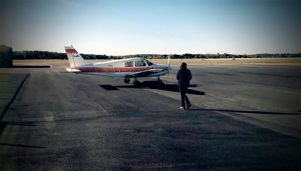 Woman pilot at airport walking to airplane, Piper Cherokee.