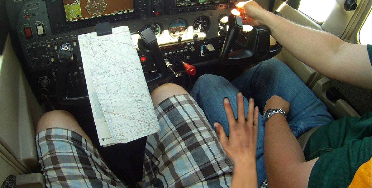 Flight training CFI at flight school, student pilot puts hand on leg using sectional chart during flight in airplane from the airport