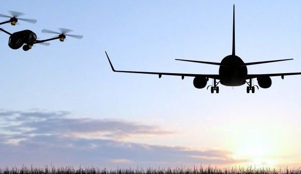 Drone hovering at departure end of runway, airplane taking off from airport runway in distance.